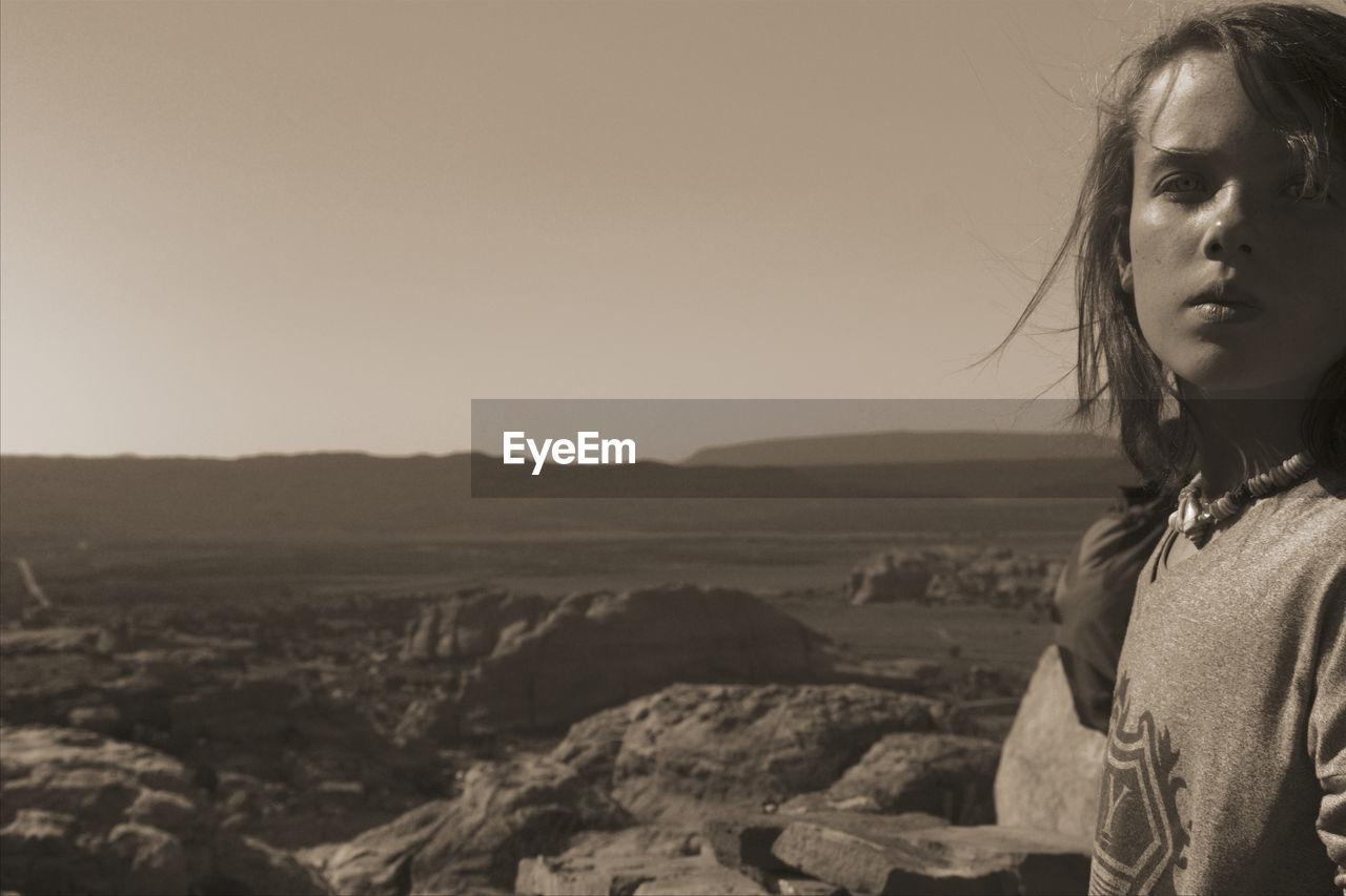 Portrait of boy in desert against clear sky