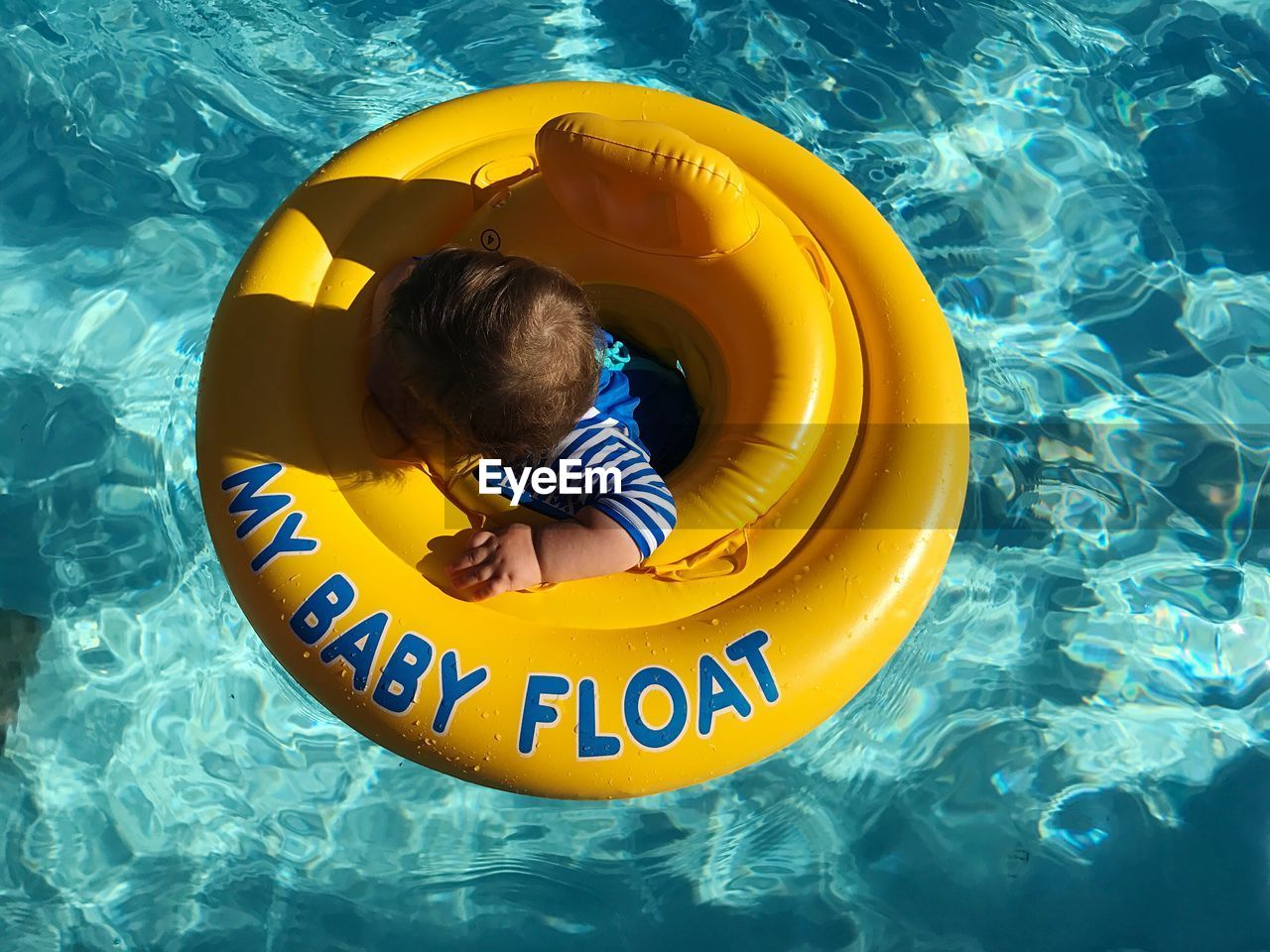 Directly Above Shot Of Baby Amidst Yellow Inflatable Ring In Swimming Pool