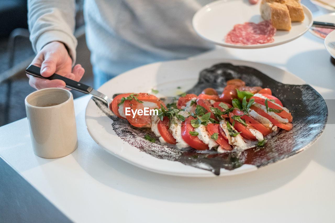 CLOSE-UP OF MAN PREPARING FOOD ON PLATE