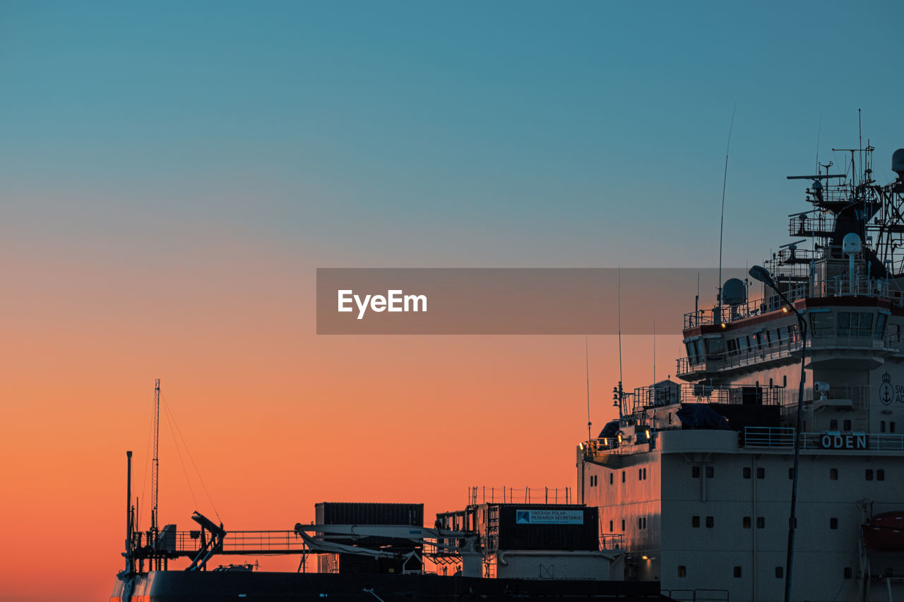 SHIP MOORED AT HARBOR DURING SUNSET