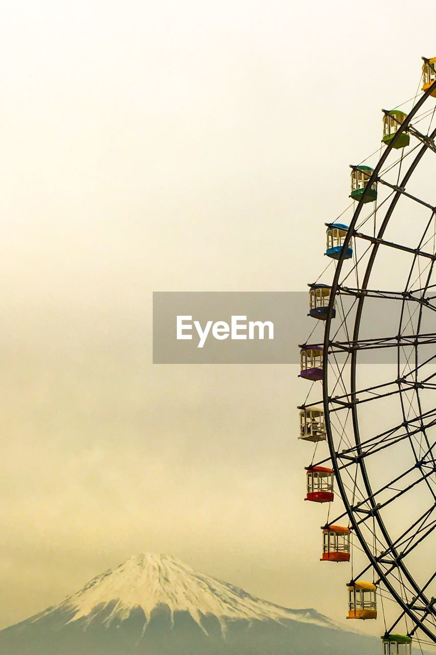 arts culture and entertainment, ferris wheel, outdoors, travel destinations, mountain, low angle view, no people, winter, clear sky, day, snow, nature, sky