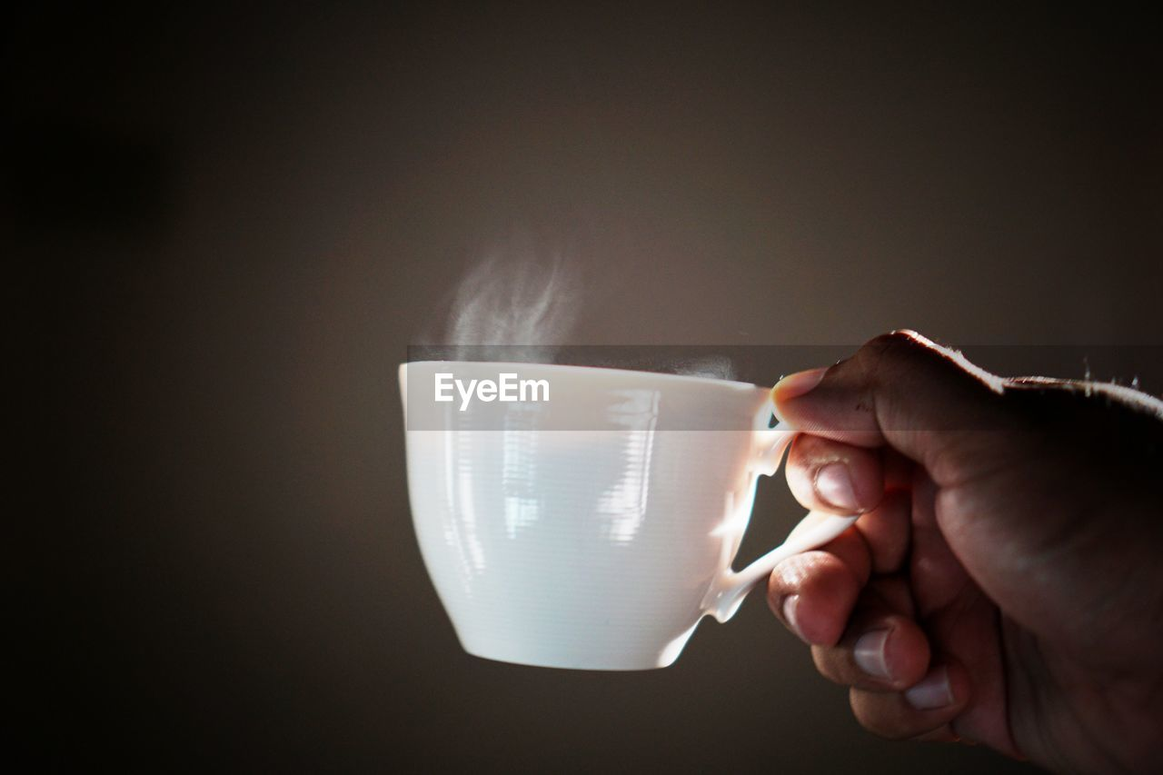 human hand, hand, cup, human body part, mug, one person, holding, coffee cup, coffee, indoors, drink, coffee - drink, real people, food and drink, refreshment, body part, lifestyles, unrecognizable person, freshness, finger, black background, tea cup, drinking