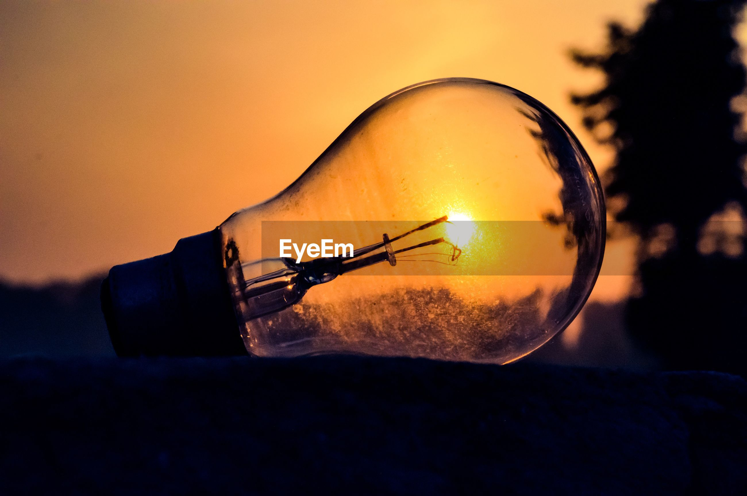 Close-up of illuminated light bulb against sky at sunset