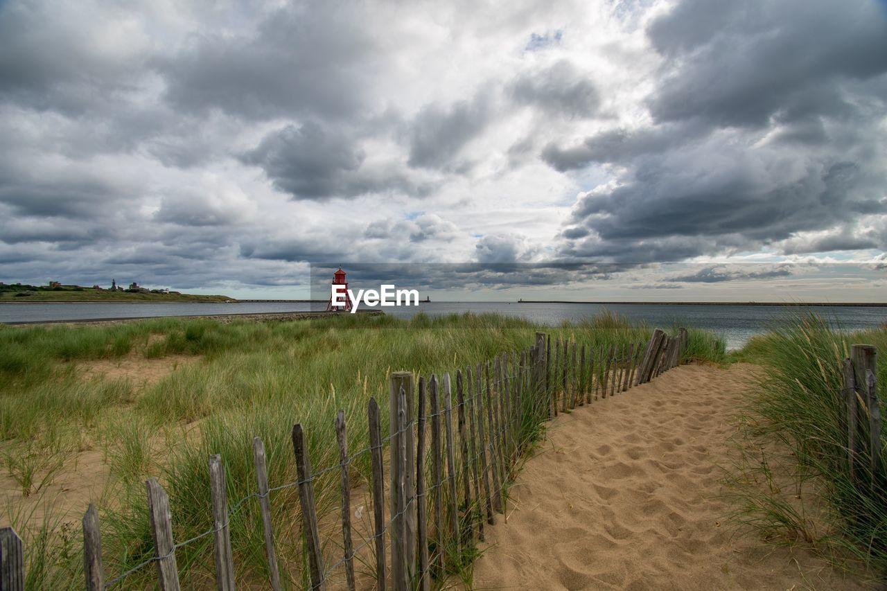 cloud - sky, sky, beauty in nature, sea, water, land, grass, scenics - nature, beach, tranquility, nature, tranquil scene, safety, sand, day, plant, no people, protection, horizon, horizon over water, outdoors, marram grass