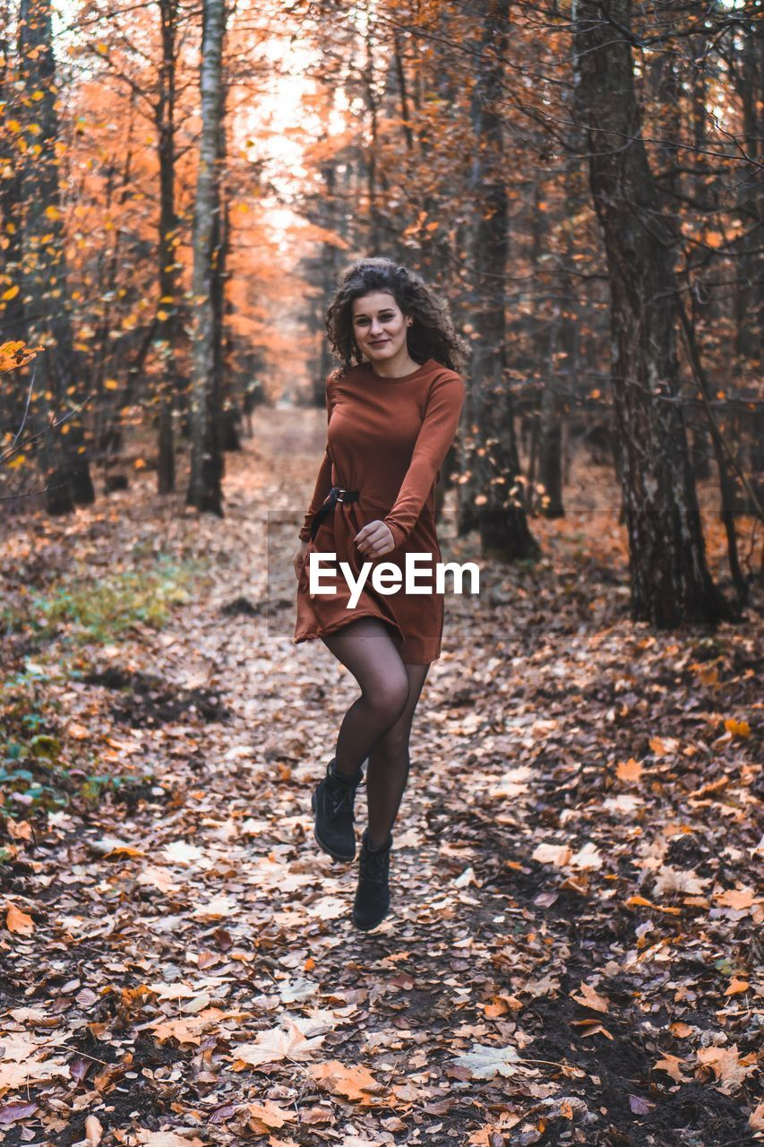 tree, one person, land, forest, full length, autumn, young adult, young women, leisure activity, real people, lifestyles, change, plant, nature, day, front view, standing, clothing, casual clothing, looking at camera, outdoors, beautiful woman, hairstyle, warm clothing