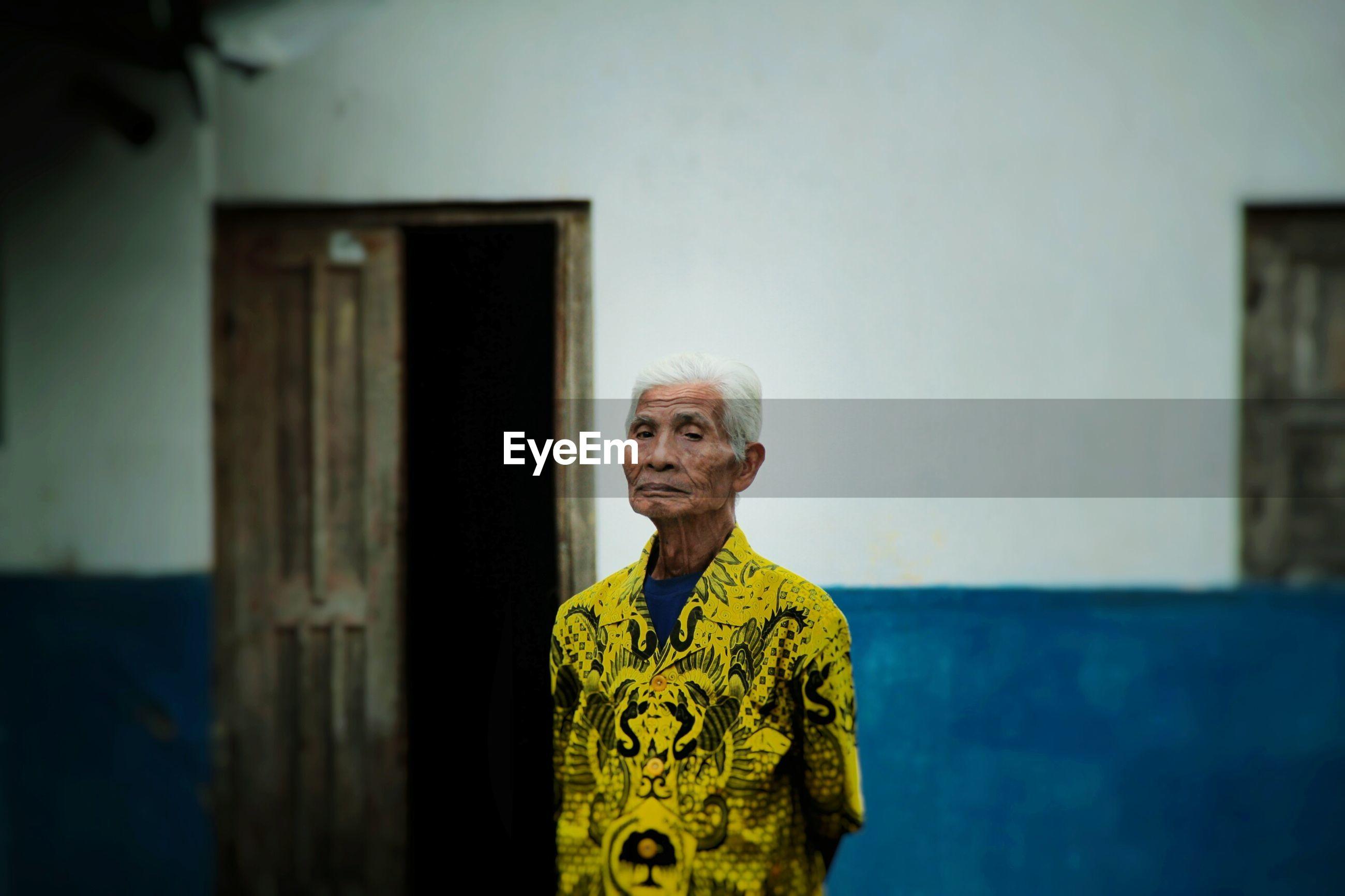 Portrait of senior man standing against wall