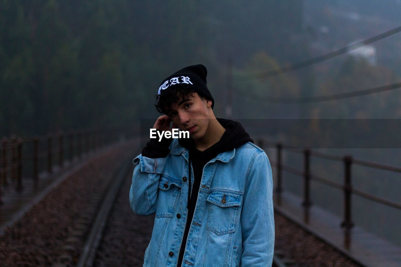 Portrait Of Young Man Standing On Railway Bridge During Foggy Weather