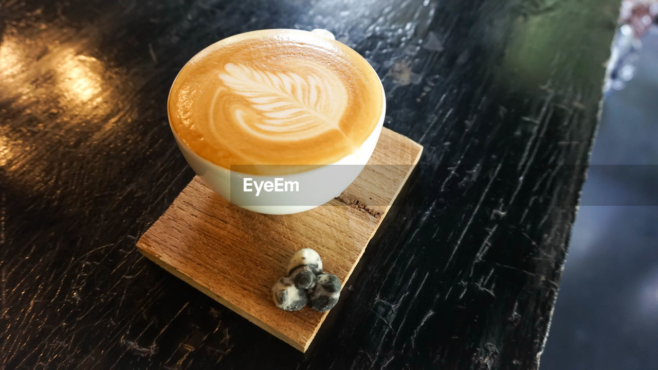 refreshment, drink, frothy drink, food and drink, coffee - drink, wood - material, cappuccino, froth art, table, coffee cup, high angle view, indoors, no people, close-up, focus on foreground, latte, freshness, day