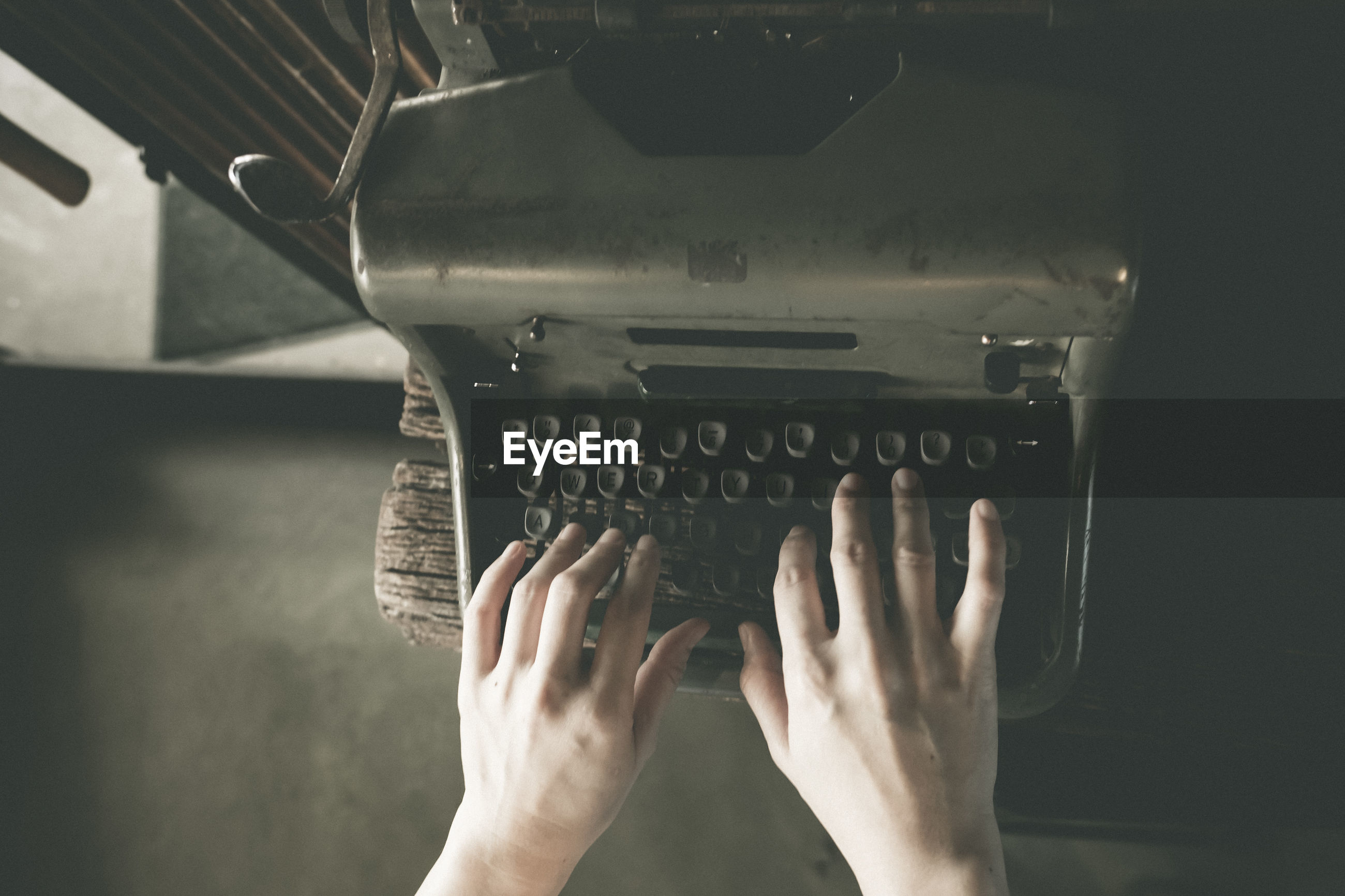 Cropped hands of person typing on typewriter
