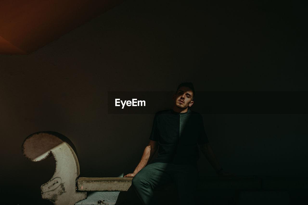 Man Sitting On Seat In Dark Room