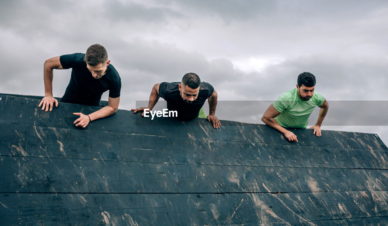 Men climbing on wall against sky