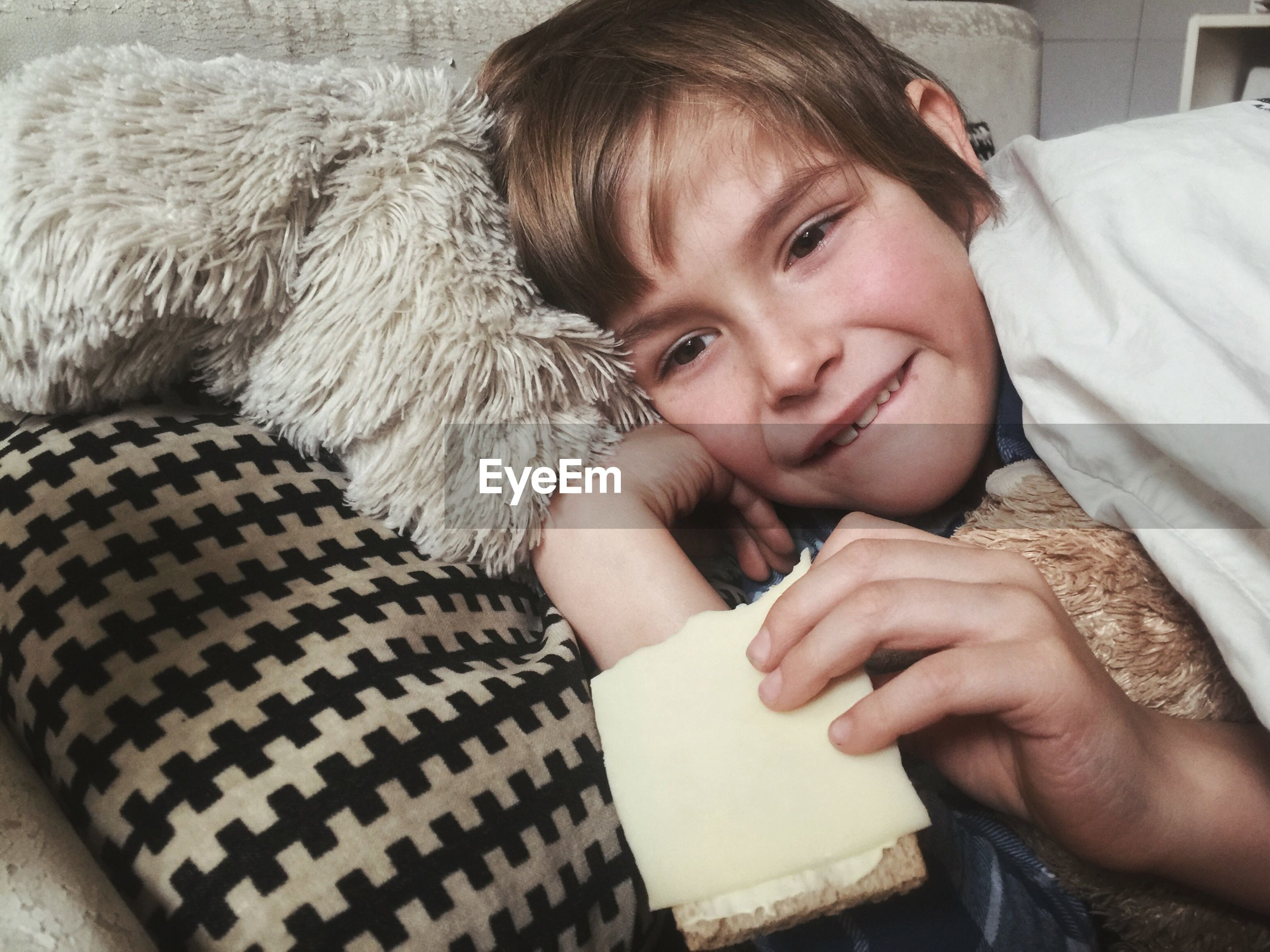 Portrait of boy eating cheese while lying on bed at home