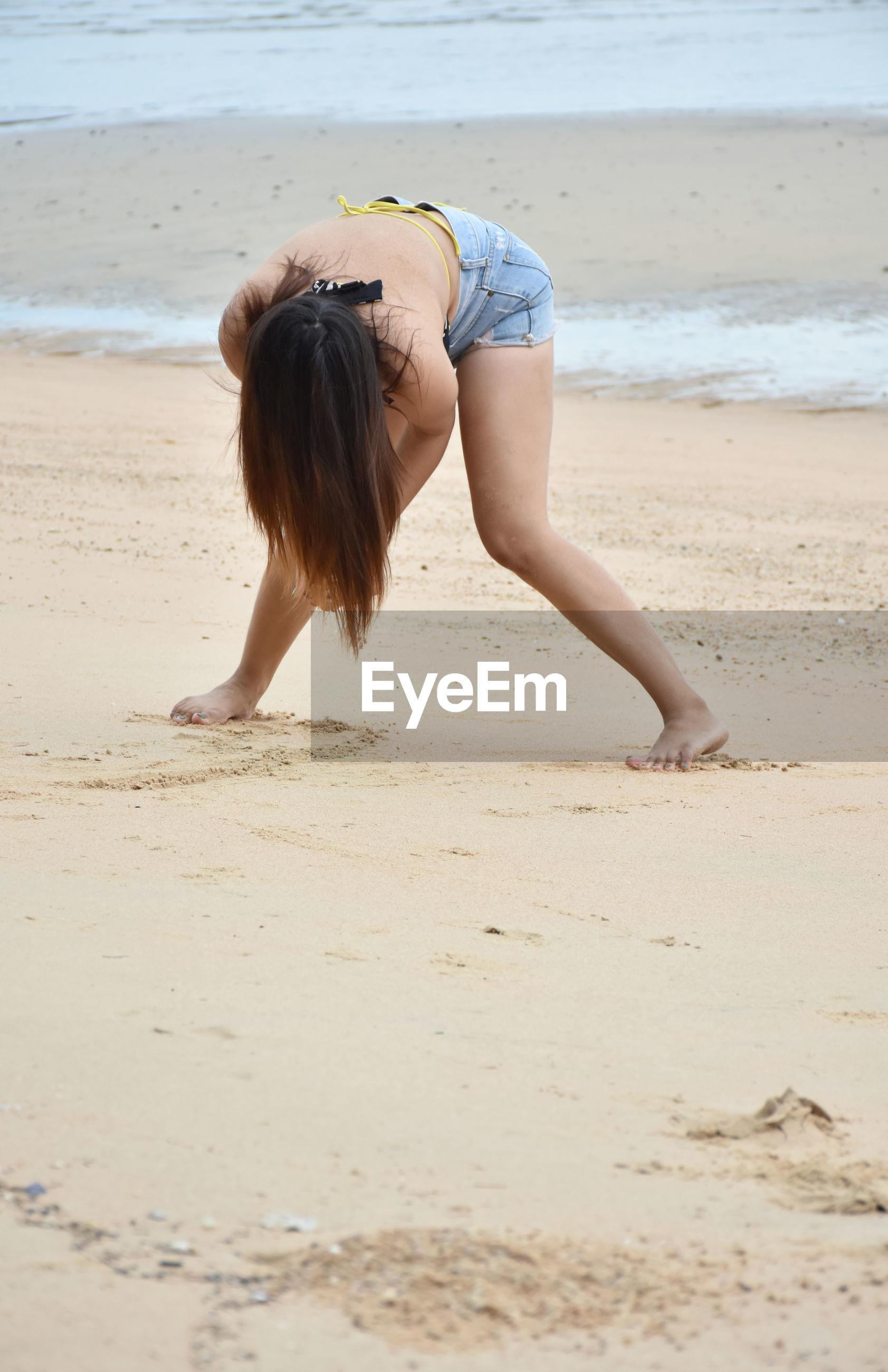 Young asian model in bikini preparing to flick hair posing action on sea beach.