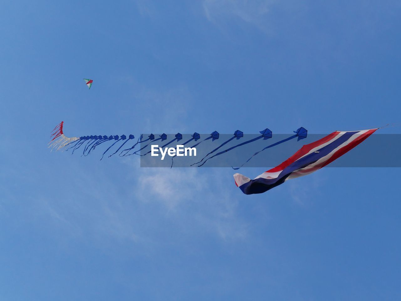 Low angle view of kite with flag flying against blue sky