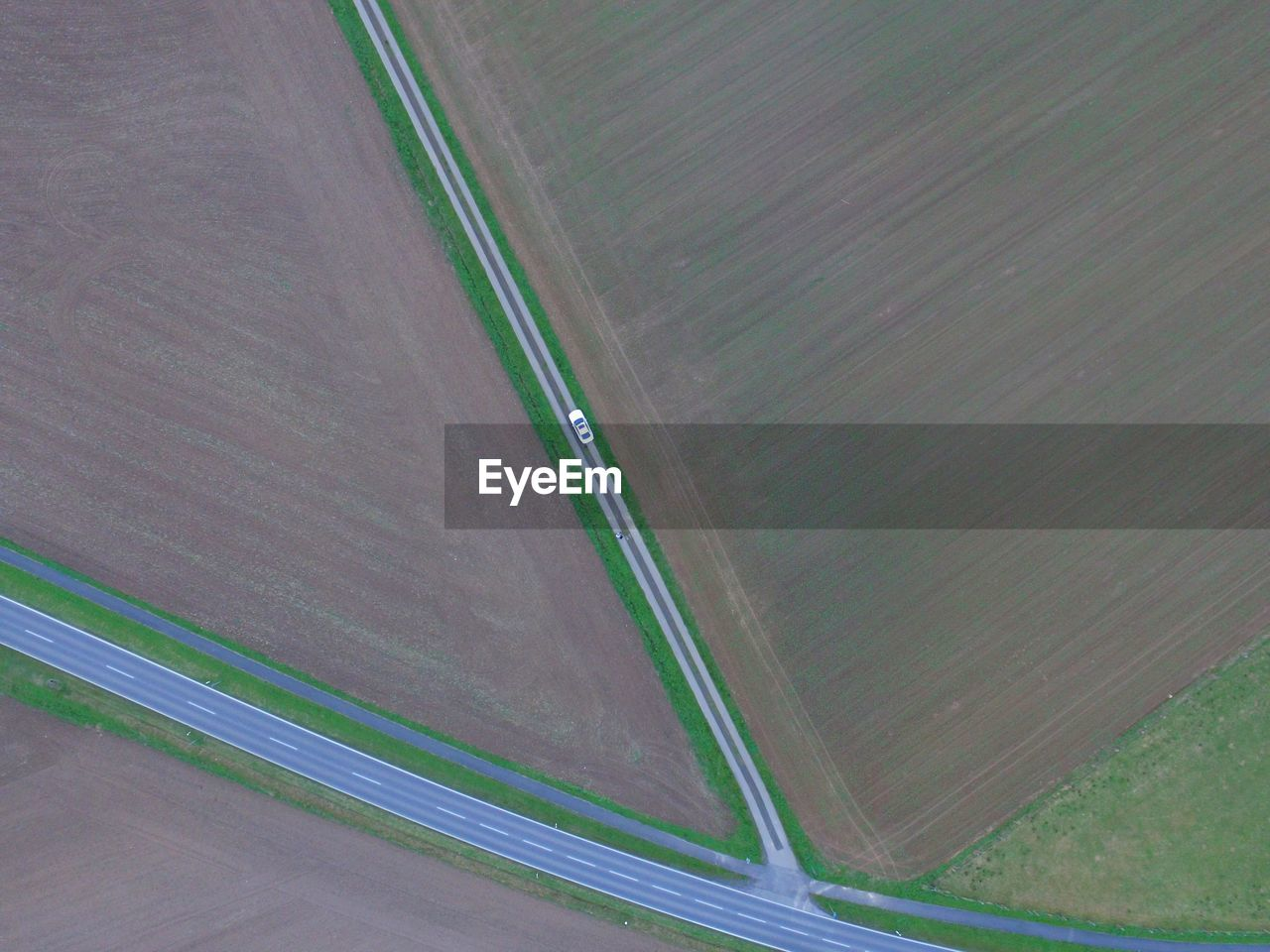 Aerial View Of Car On Road Amidst Agricultural Field