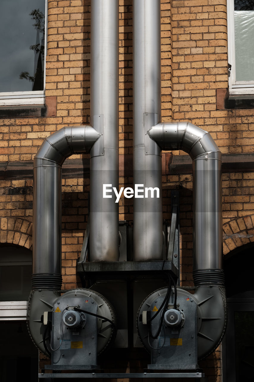 pipe - tube, industry, built structure, no people, metal, brick, architecture, building exterior, pipeline, brick wall, factory, equipment, machinery, connection, technology, fuel and power generation, wall, outdoors, day, close-up, silver colored, meter - instrument of measurement, industrial equipment