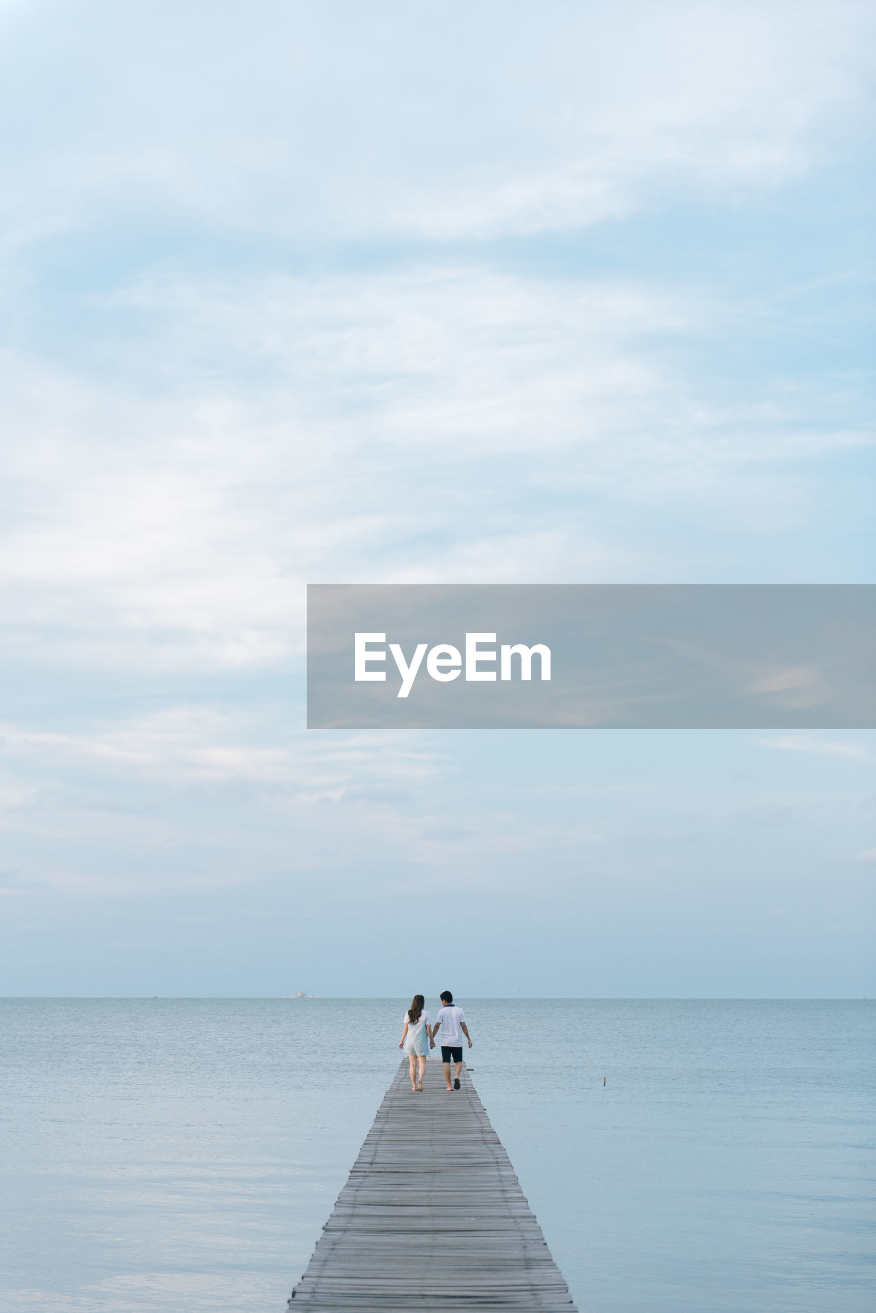 Rear view of couple walking on pier over sea against cloudy sky