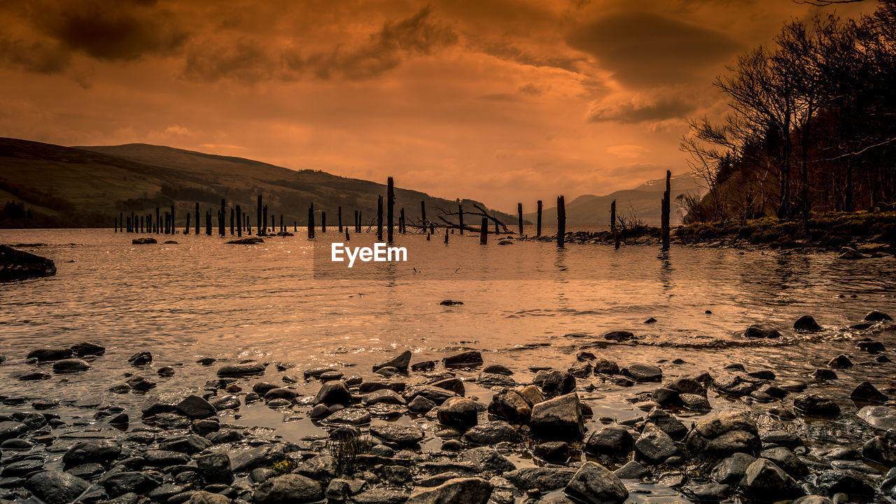 sky, water, sunset, cloud - sky, beauty in nature, scenics - nature, tranquility, nature, tranquil scene, no people, rock, bridge, sea, land, solid, architecture, beach, non-urban scene, built structure, bridge - man made structure