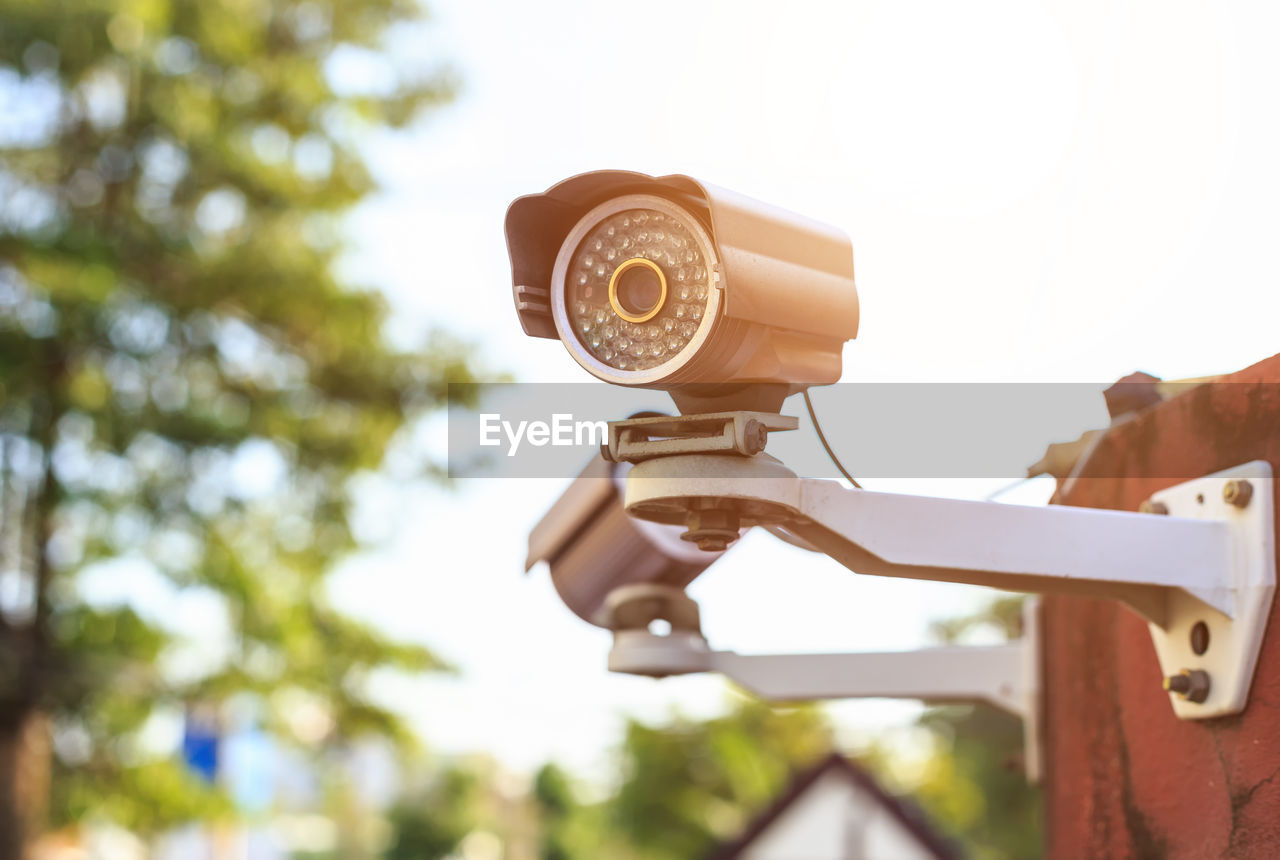focus on foreground, tree, technology, day, close-up, nature, plant, outdoors, no people, architecture, low angle view, built structure, sunlight, security, white color, building exterior, sky, photography themes, optical instrument, surveillance, hand-held telescope