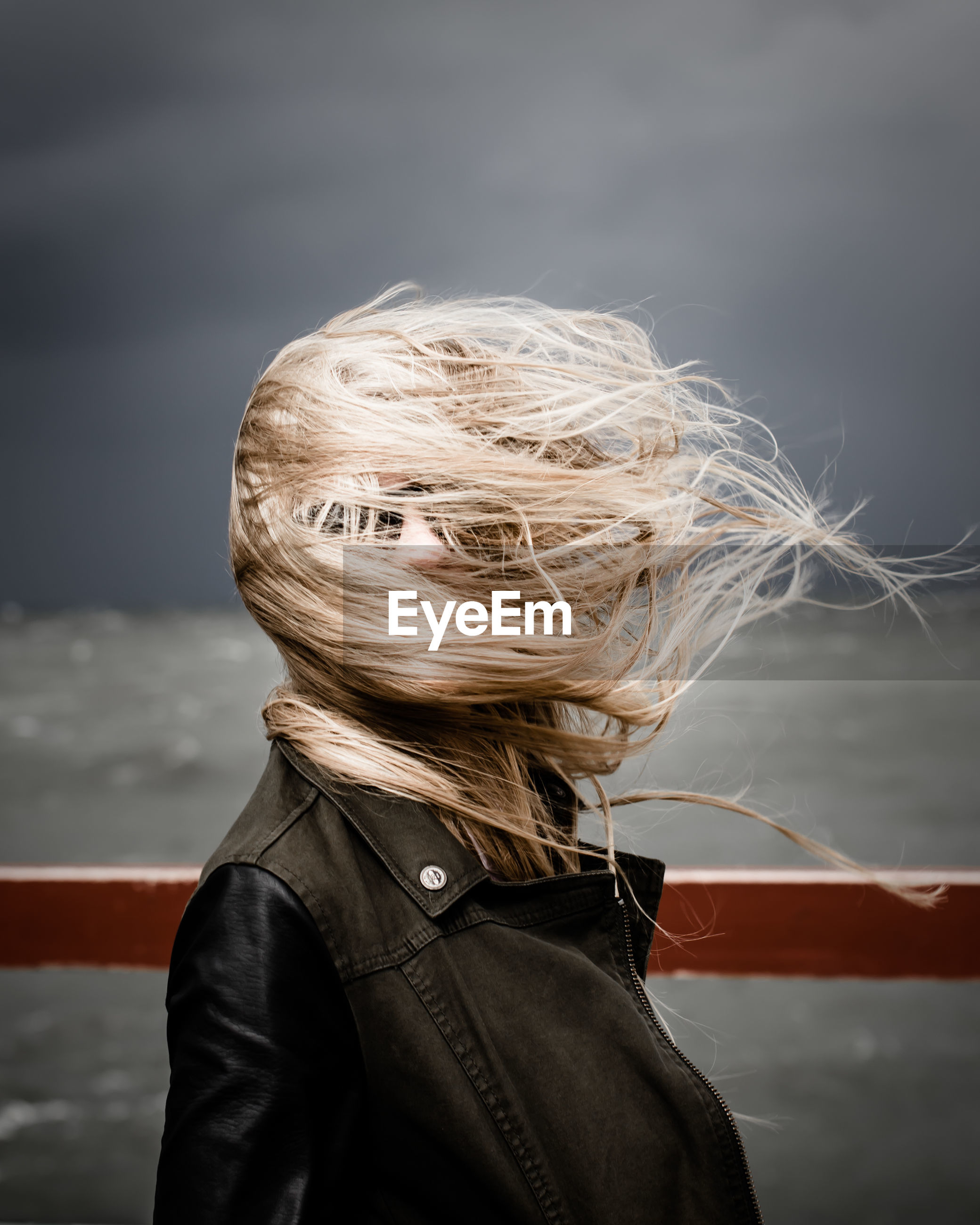 Woman with obscured face standing by railing against cloudy sky