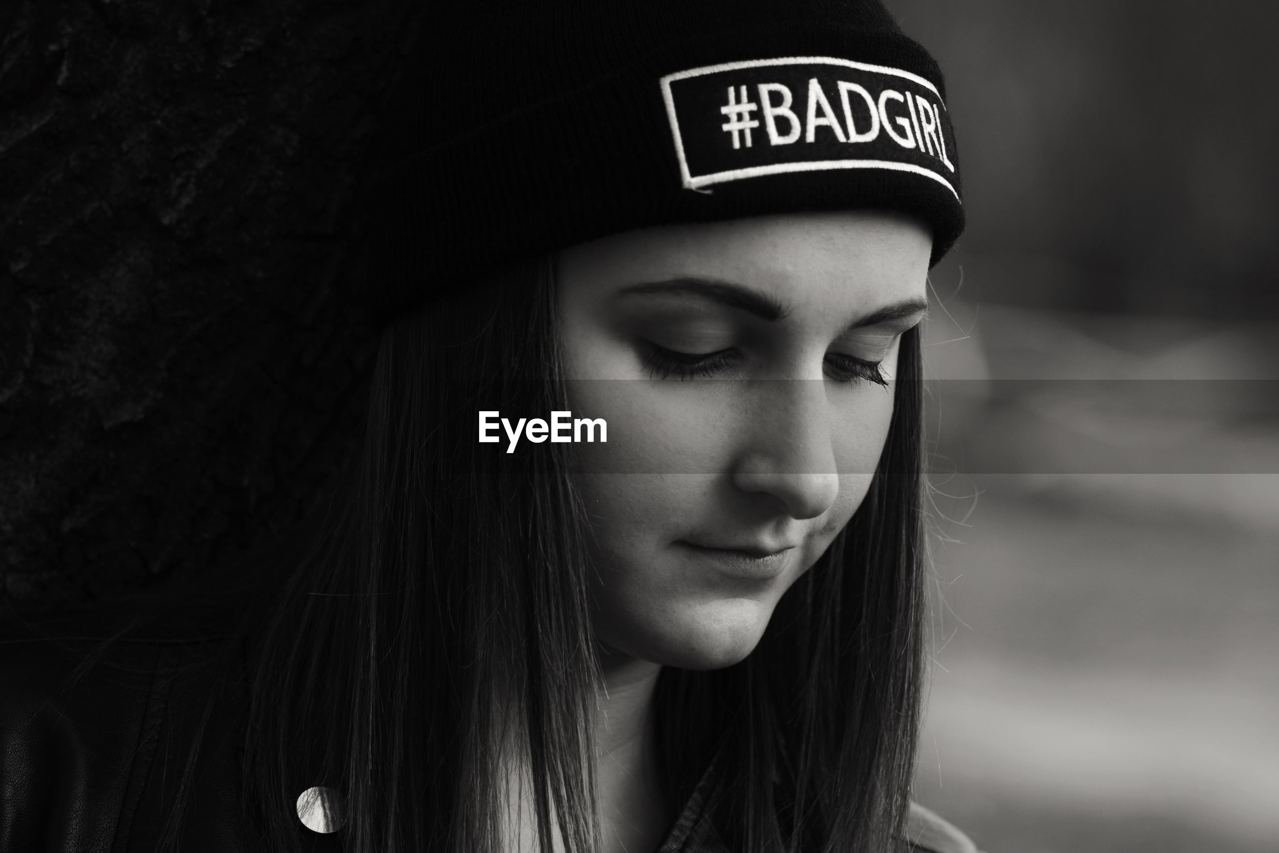 Thoughtful beautiful woman wearing knit hat with text on it