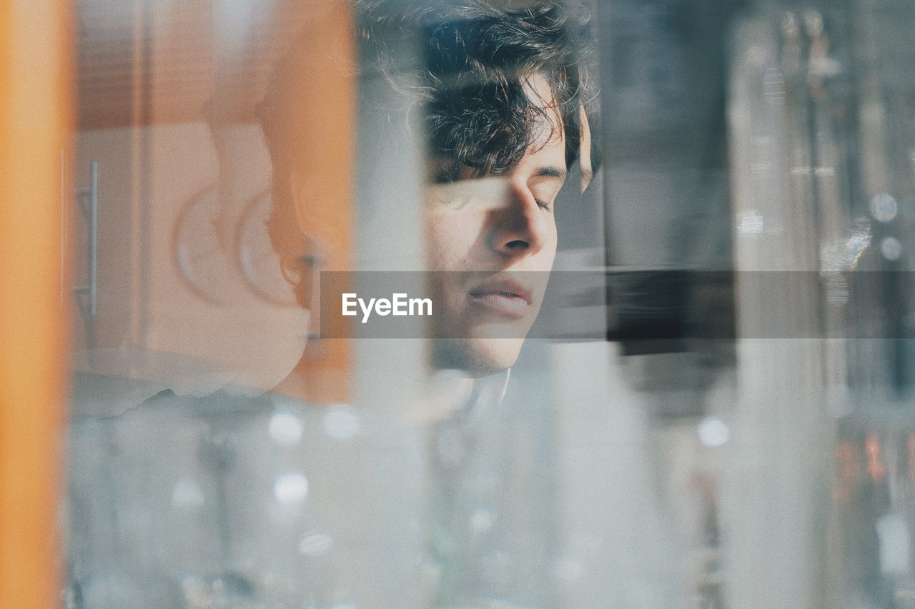 Close-up of young man seen through glass window