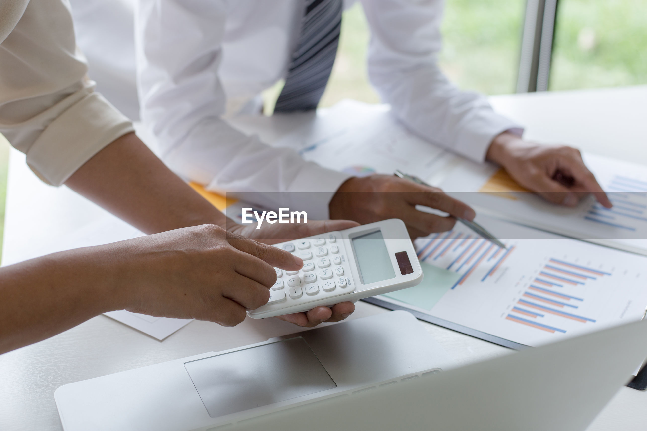 Midsection of businessman with female colleague using calculator at office