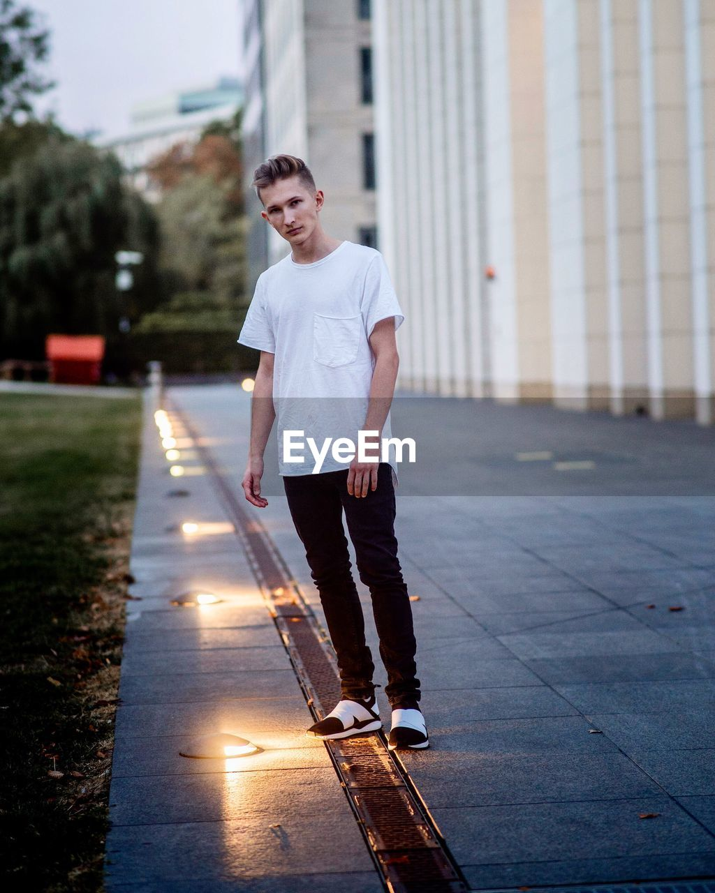Portrait of young man standing by illuminated recessed lights on footpath