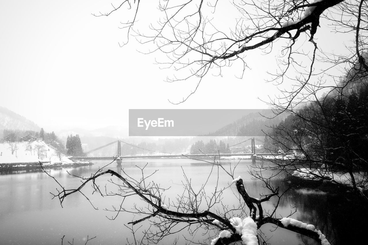 bare tree, water, winter, mountain, nature, tree, cold temperature, weather, beauty in nature, branch, snow, fog, lake, no people, outdoors, day, sky, tranquility, scenics