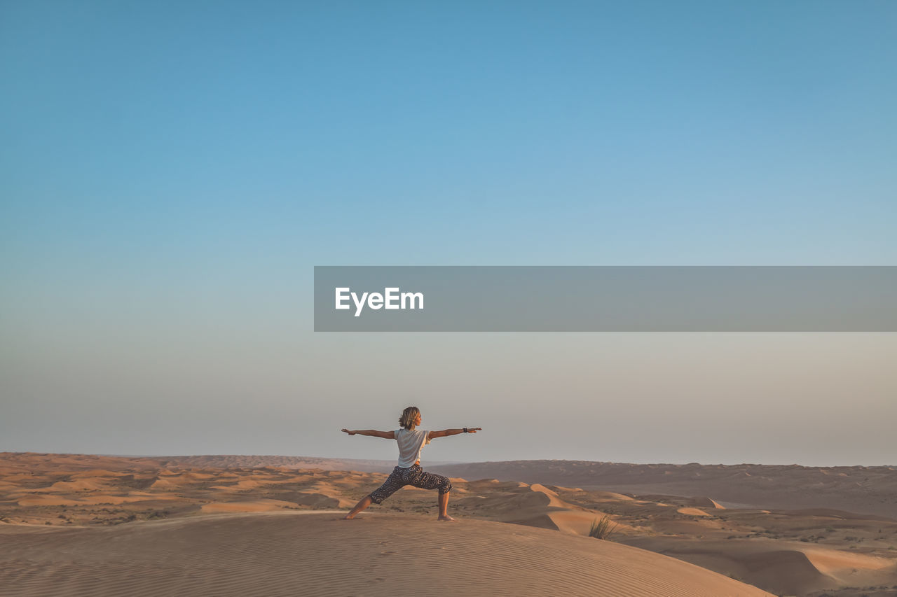 Woman Practicing Yoga In Desert
