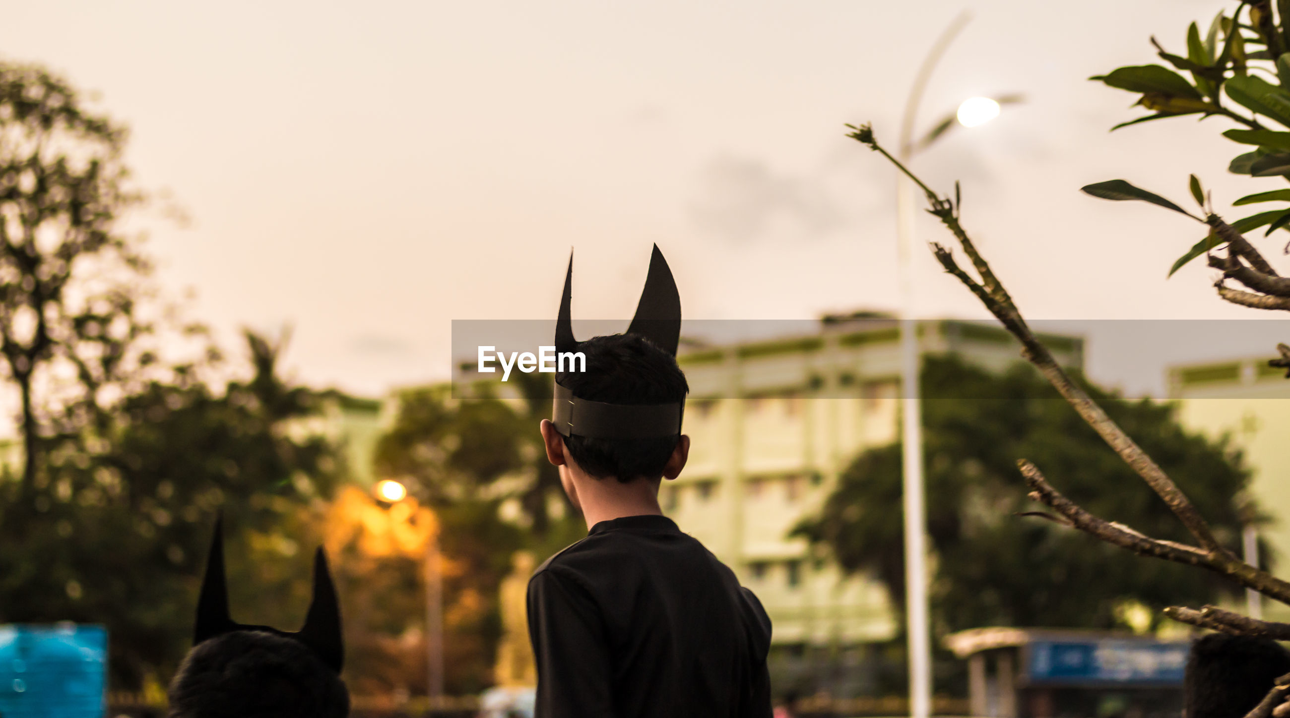 Rear view of boy wearing horn mask against clear sky