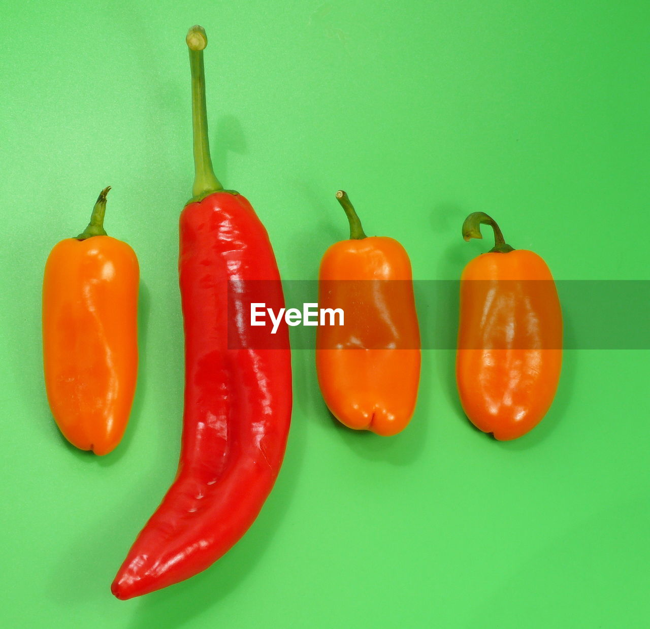 Close-up of chili peppers on green background