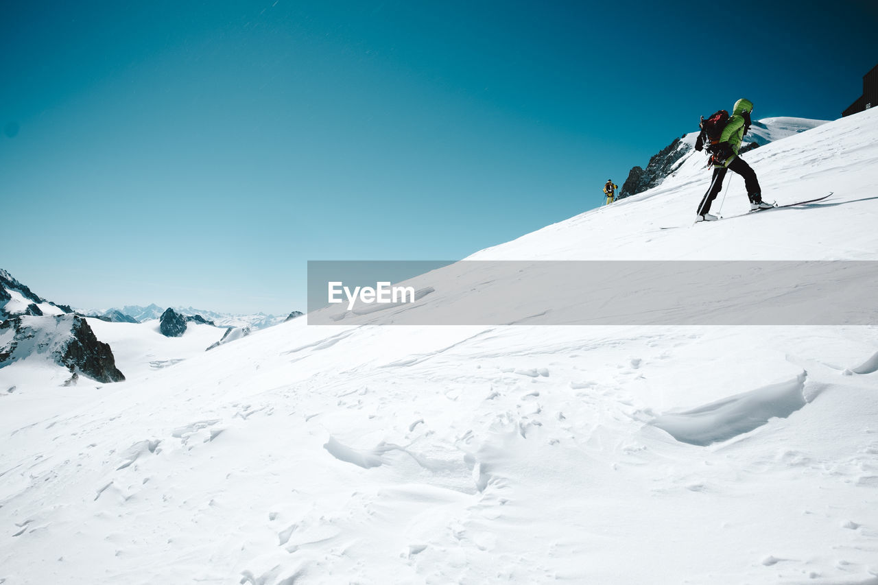 Person On Snow Covered Mountain Against Clear Blue Sky