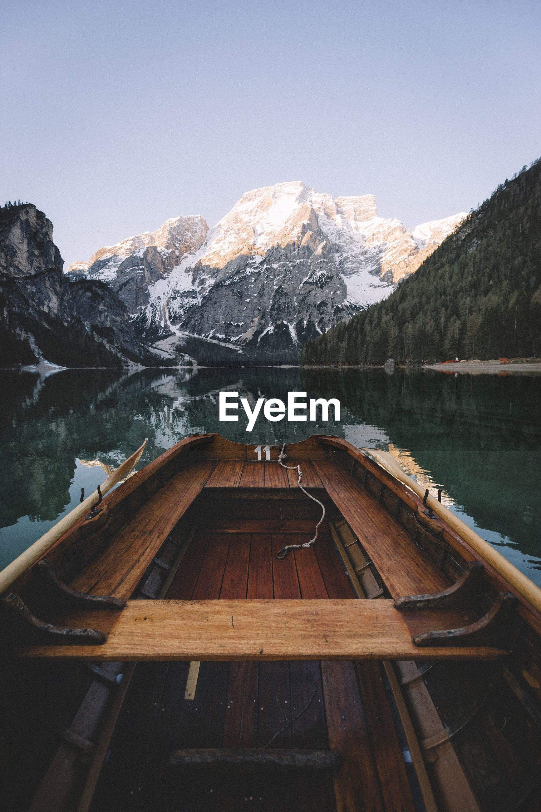Wooden boat in river against mountain