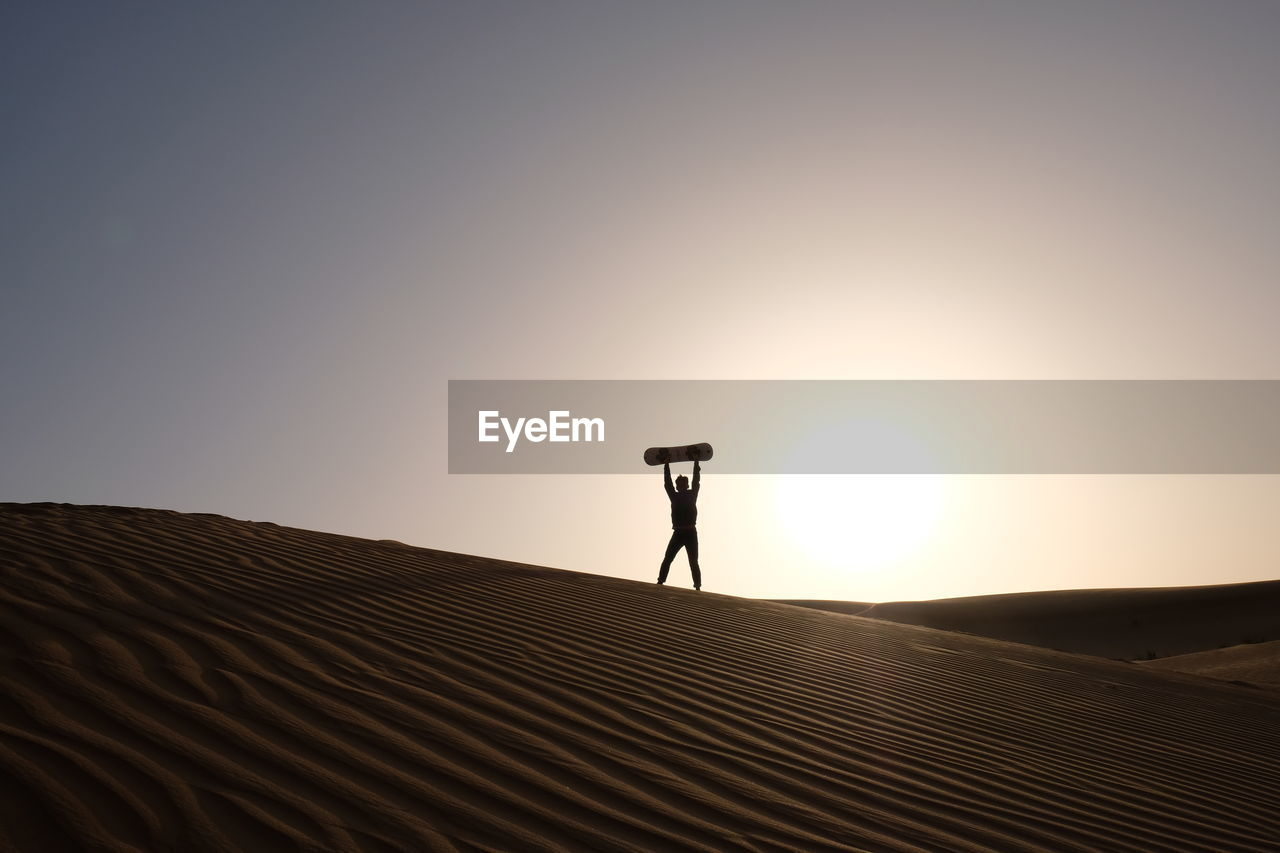 sky, desert, real people, sand, lifestyles, sand dune, arid climate, scenics - nature, land, landscape, climate, nature, leisure activity, standing, one person, beauty in nature, clear sky, tranquil scene, tranquility, sunset, outdoors