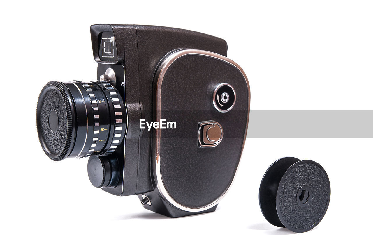 white background, black color, technology, studio shot, cut out, photography themes, camera - photographic equipment, single object, still life, indoors, retro styled, no people, camera, photographic equipment, equipment, lens - optical instrument, close-up, digital camera, copy space, personal accessory, slr camera, home video camera