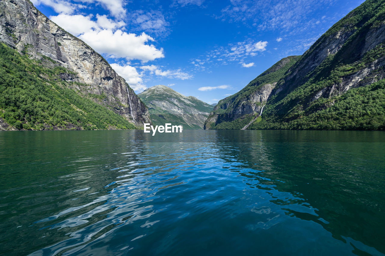 water, mountain, beauty in nature, scenics - nature, waterfront, cloud - sky, sky, tranquil scene, tranquility, lake, nature, non-urban scene, mountain range, day, idyllic, reflection, no people, nautical vessel, outdoors, formation