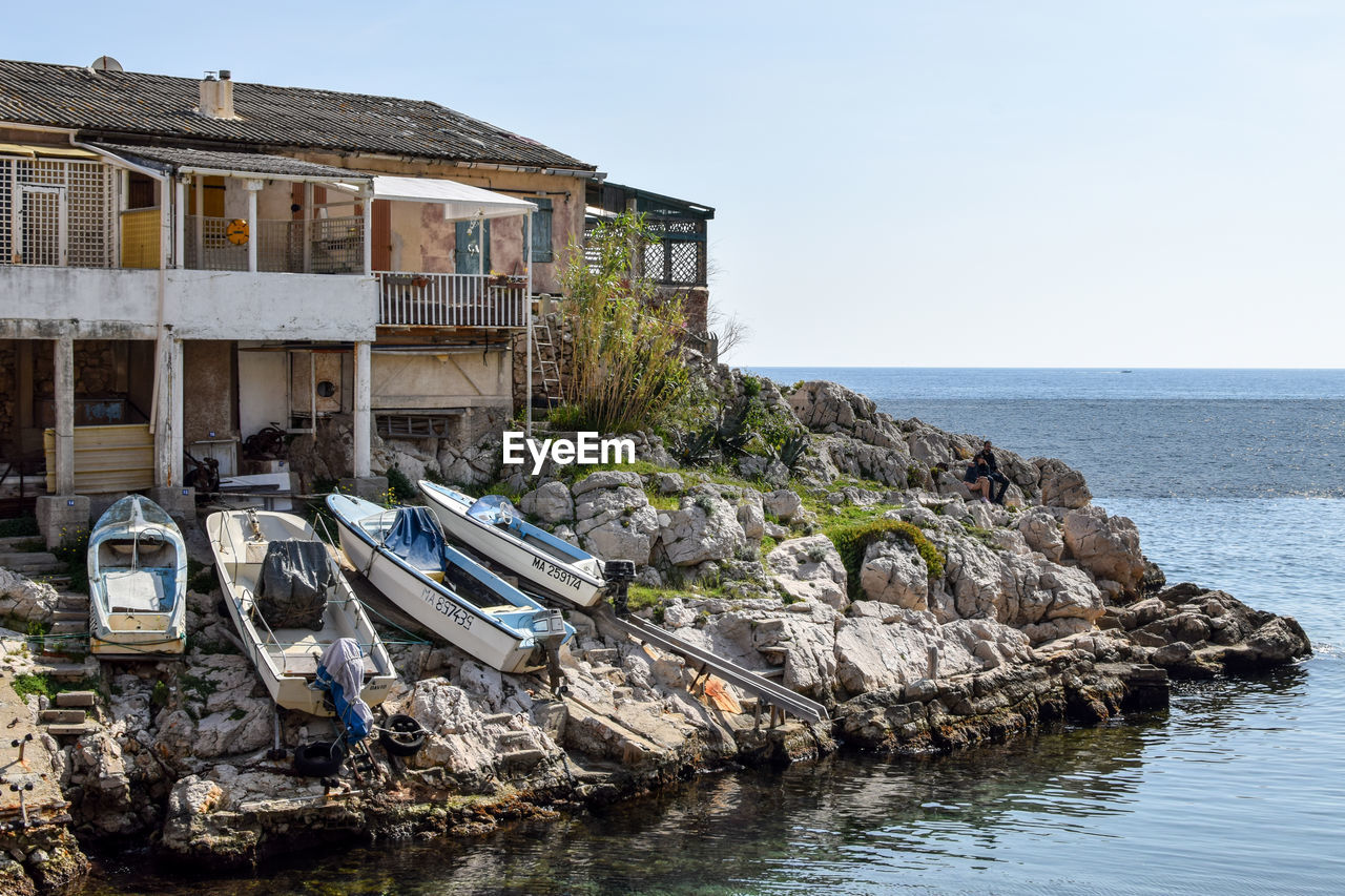 sea, water, built structure, architecture, rock - object, horizon over water, building exterior, house, day, no people, clear sky, outdoors, beach, nature, scenics, sky