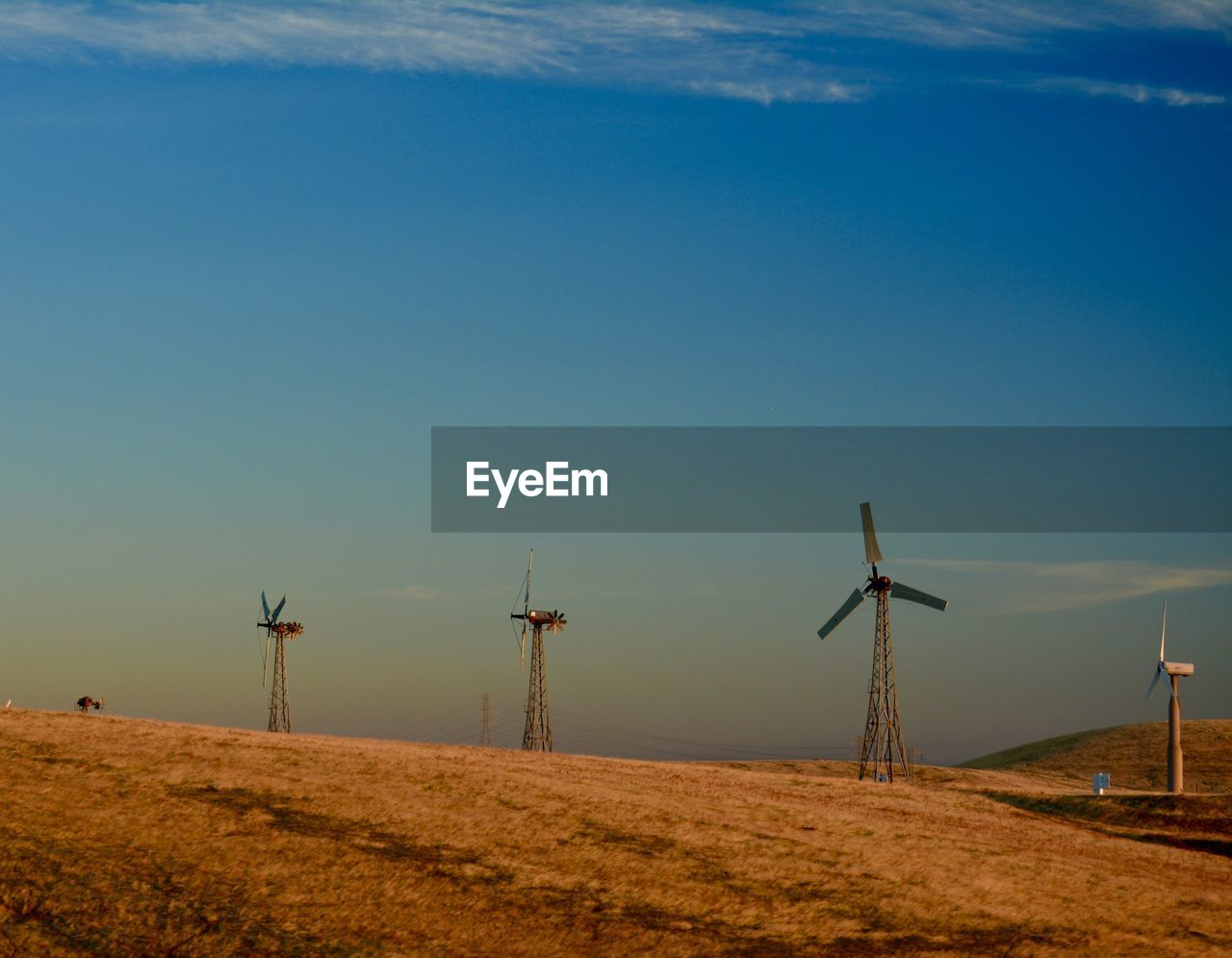 sky, wind turbine, environment, alternative energy, environmental conservation, renewable energy, fuel and power generation, turbine, wind power, landscape, field, land, nature, scenics - nature, beauty in nature, tranquil scene, rural scene, blue, tranquility, non-urban scene, outdoors, no people, sustainable resources