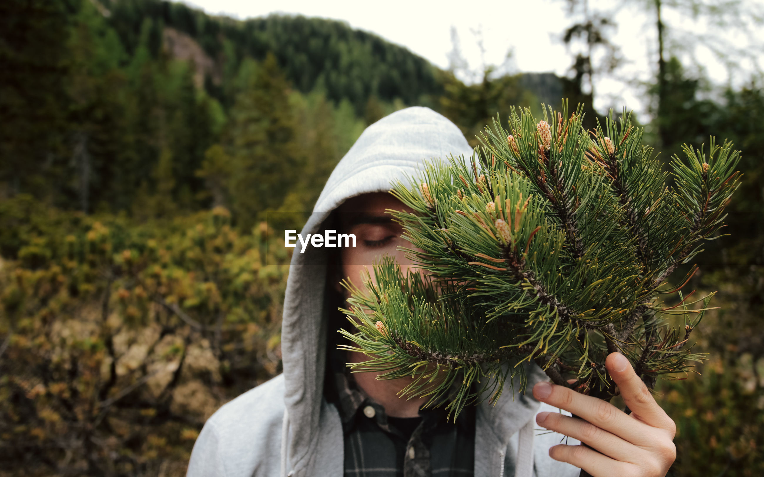 Close-up of man with eyes closed holding plants in forest