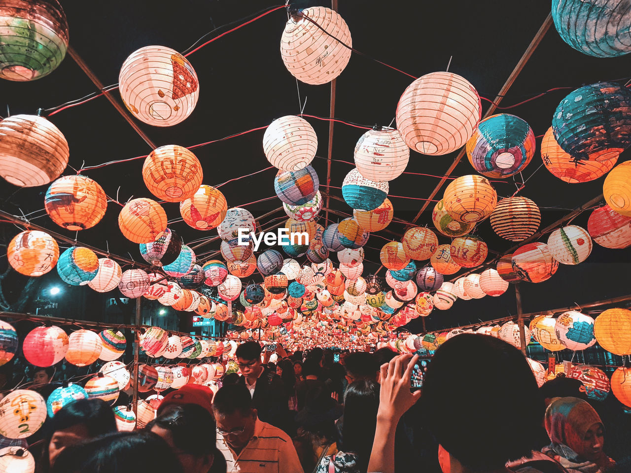 lantern, night, lighting equipment, decoration, hanging, chinese lantern, low angle view, group of people, large group of objects, illuminated, celebration, large group of people, abundance, real people, lifestyles, men, leisure activity, festival, paper lantern, outdoors