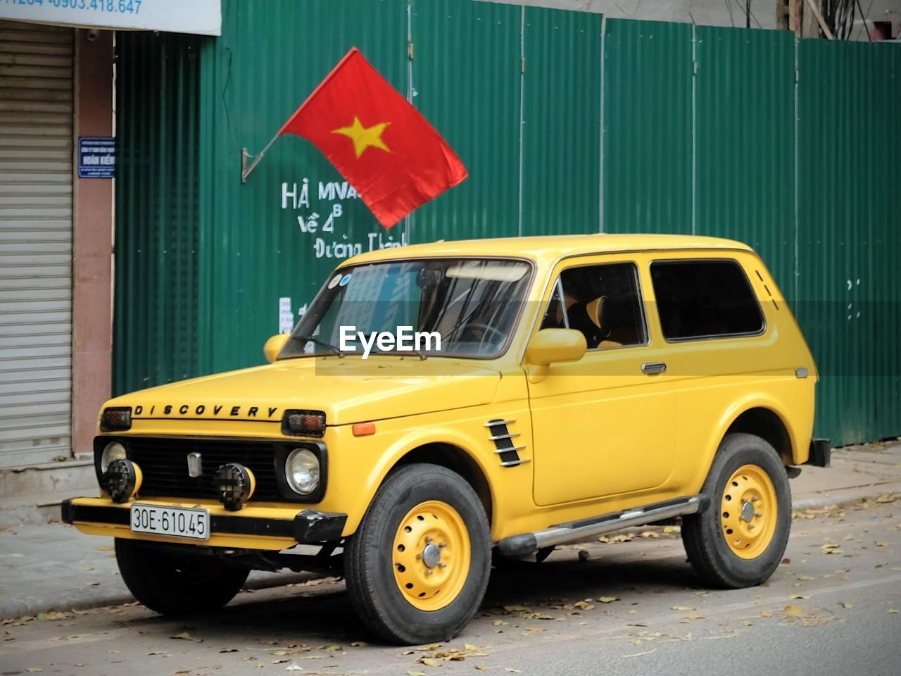 land vehicle, transportation, mode of transport, car, yellow, outdoors, flag, day, patriotism, no people