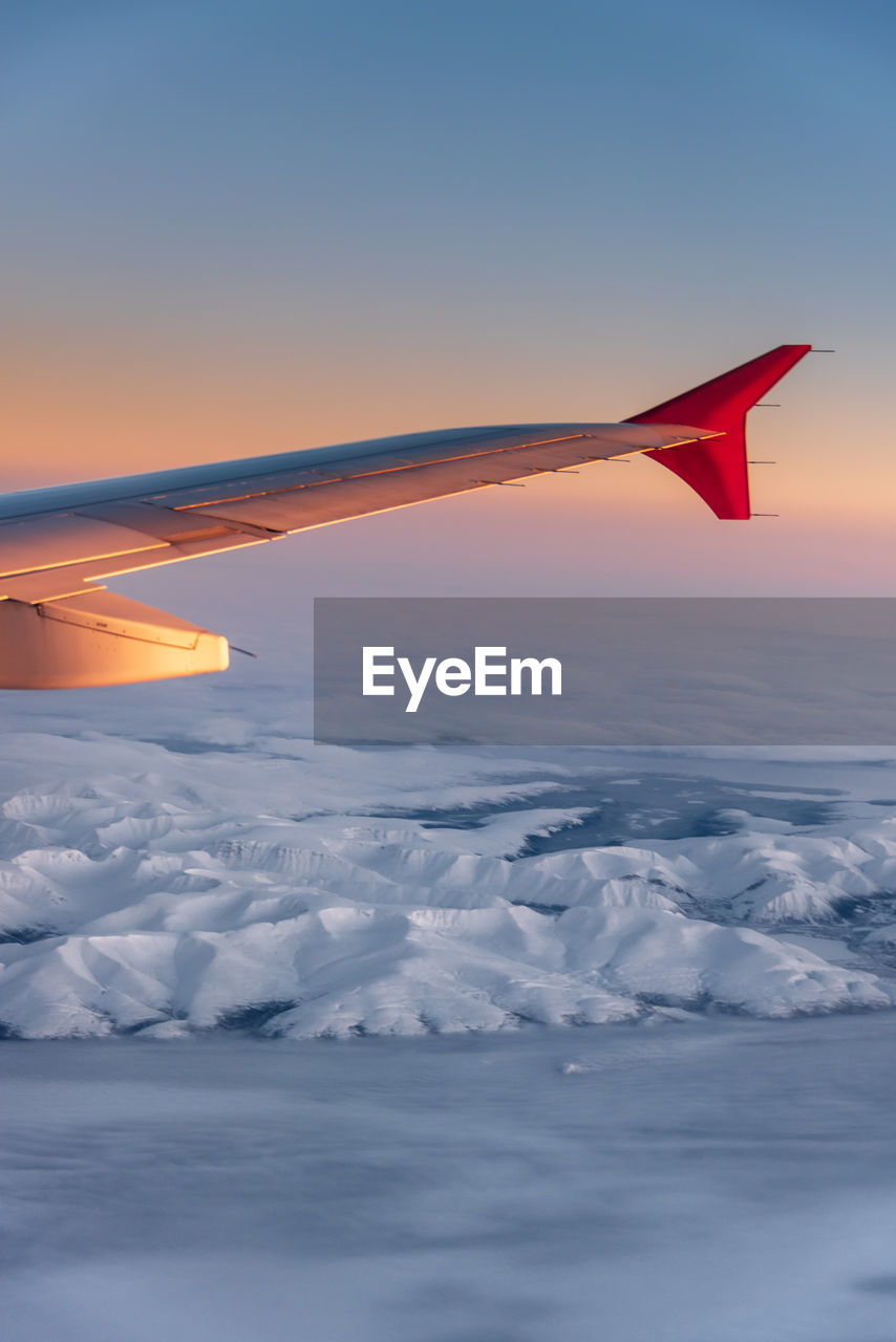 sky, sunset, beauty in nature, scenics - nature, no people, orange color, aircraft wing, nature, airplane, cloud - sky, air vehicle, cold temperature, winter, red, tranquil scene, mid-air, flying, tranquility, transportation, snowcapped mountain