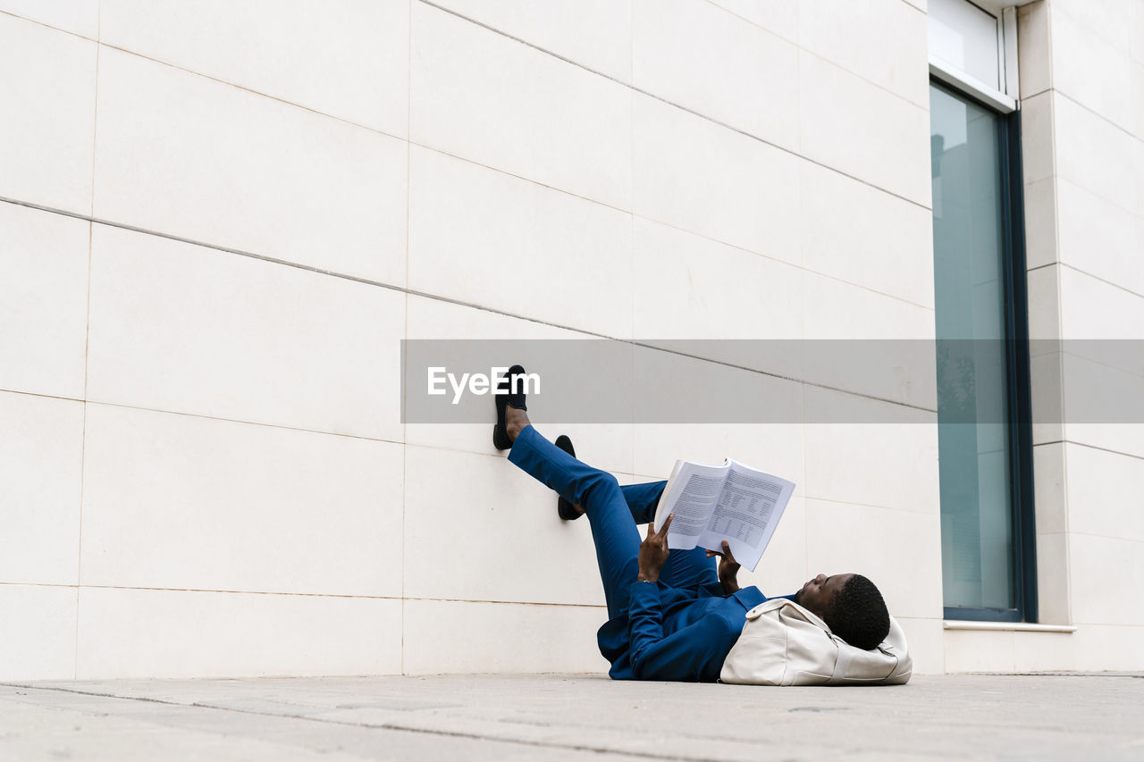MAN SITTING ON WALL AGAINST BUILDING