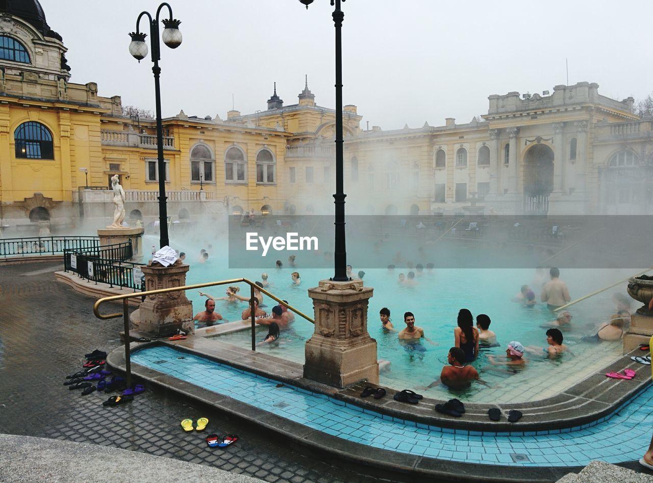 People Enjoying In Swimming Pool Against Building