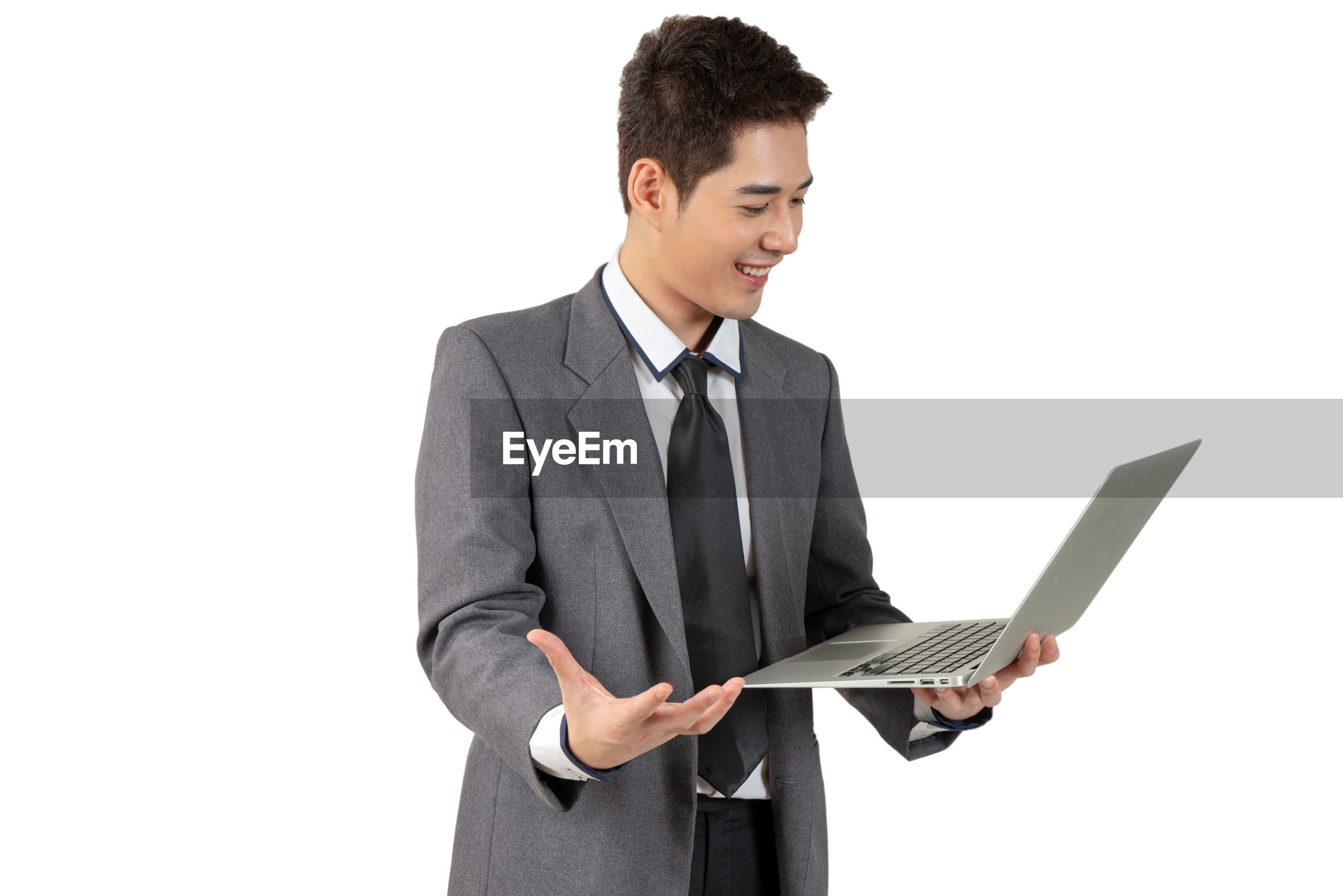 Smiling young businessman holding laptop against white background