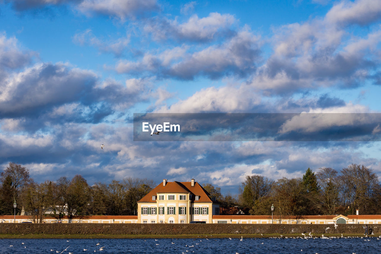 cloud - sky, built structure, architecture, sky, building exterior, building, water, tree, house, no people, plant, nature, day, lake, beauty in nature, waterfront, animal, residential district, animal themes, outdoors