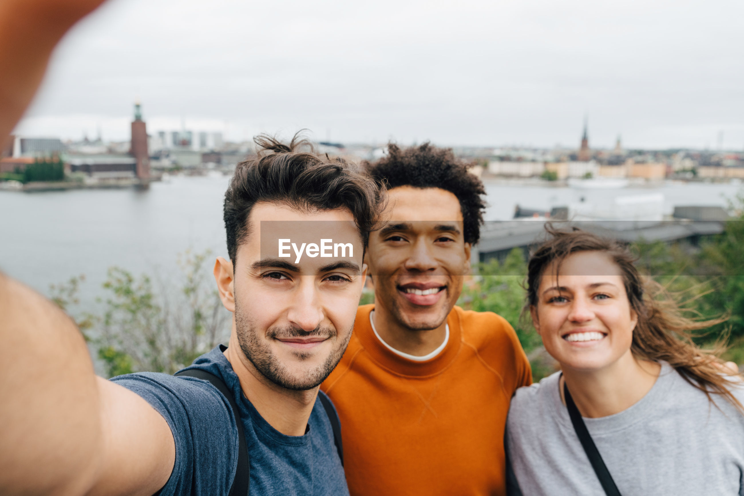 PORTRAIT OF SMILING YOUNG COUPLE IN CITY AT PARK