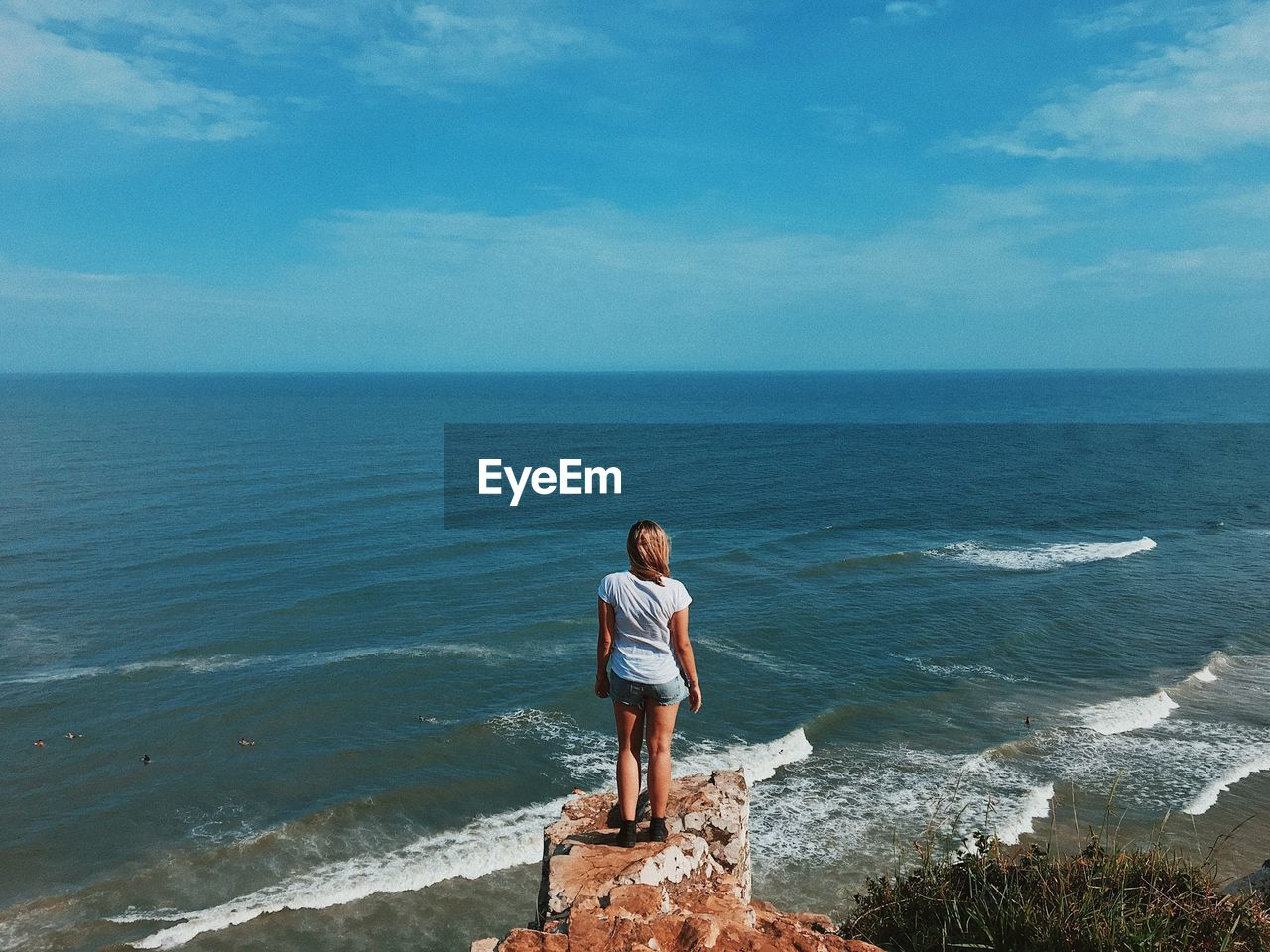 sea, horizon over water, water, nature, standing, real people, scenics, sky, one person, beauty in nature, leisure activity, full length, tranquil scene, day, outdoors, rear view, casual clothing, tranquility, lifestyles, young adult, vacations, beach, blue, wave, young women
