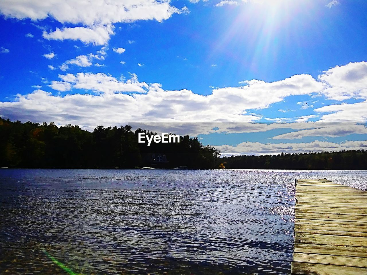 sky, water, cloud - sky, tree, beauty in nature, lake, plant, sunlight, scenics - nature, tranquil scene, tranquility, nature, day, no people, non-urban scene, sun, lens flare, wood - material, sunbeam, outdoors